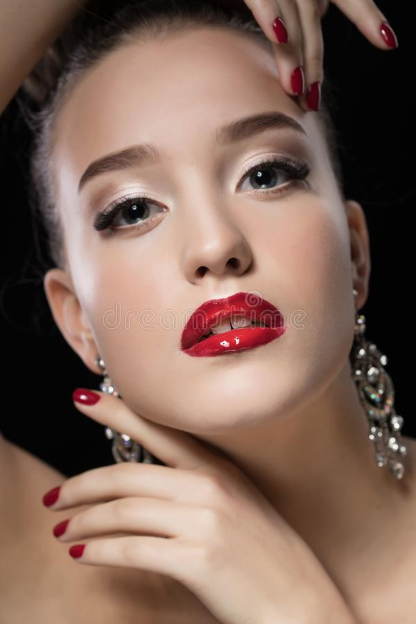 Beauty Girl with Red Lips and Nails. Luxury Woman, jewelery earrings. royalty free stock image