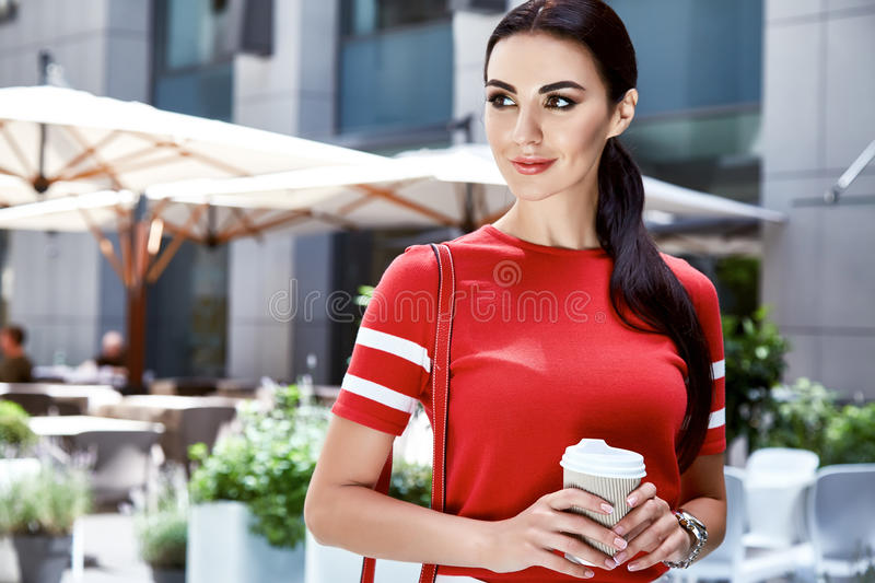 Beauty woman model summer collection long brunette hair. Perfect body shape walk on the street fashion style clothes wear t-shirt drink coffee city accessory stock images