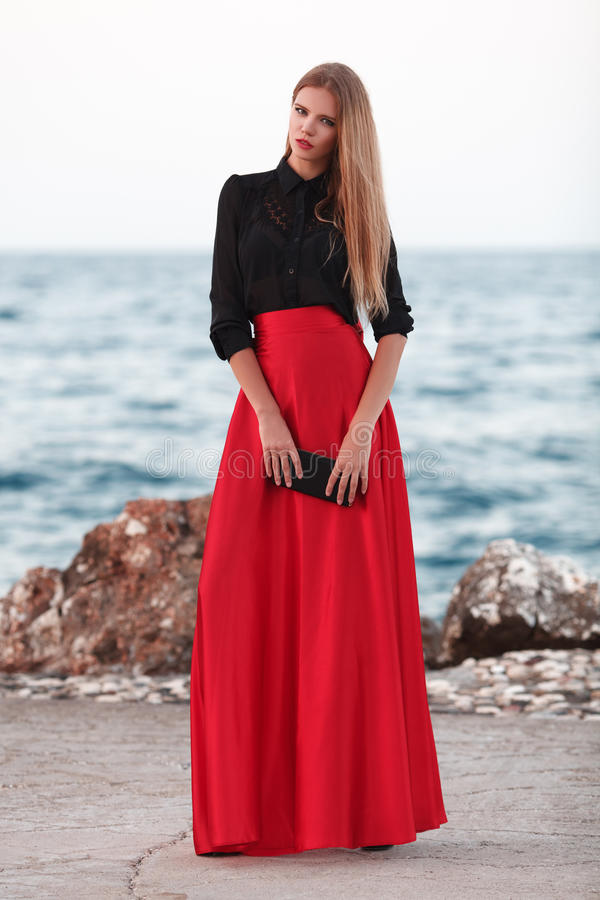 beauty woman in red dress at the coast. Fashion woman royalty free stock images