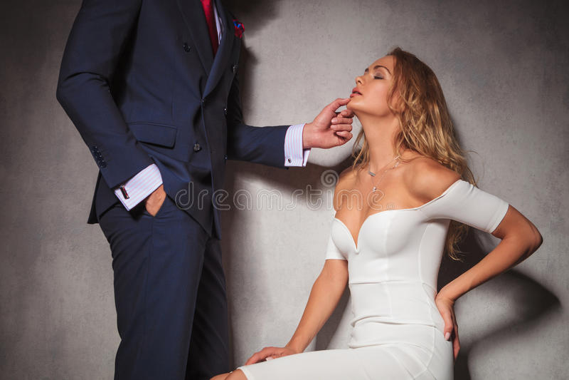 Sexy beeld van een heer die zijn vrouw houden door haar kin stock fotografie