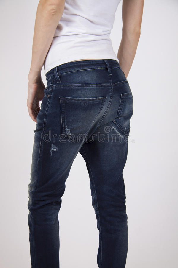 Sexy benen in donkere sportieve jeans stock afbeelding