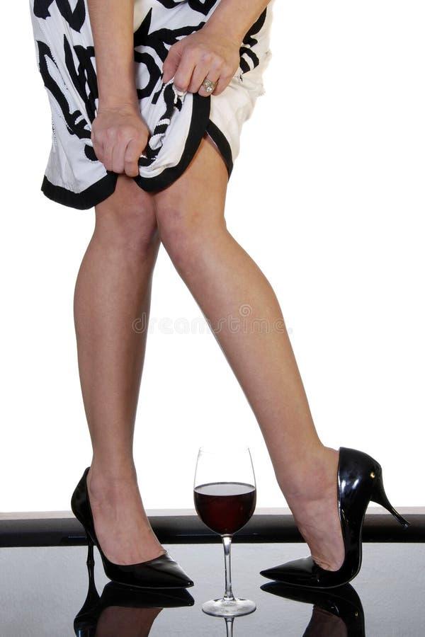 Sexy benen met glas rode wijn royalty-vrije stock afbeelding