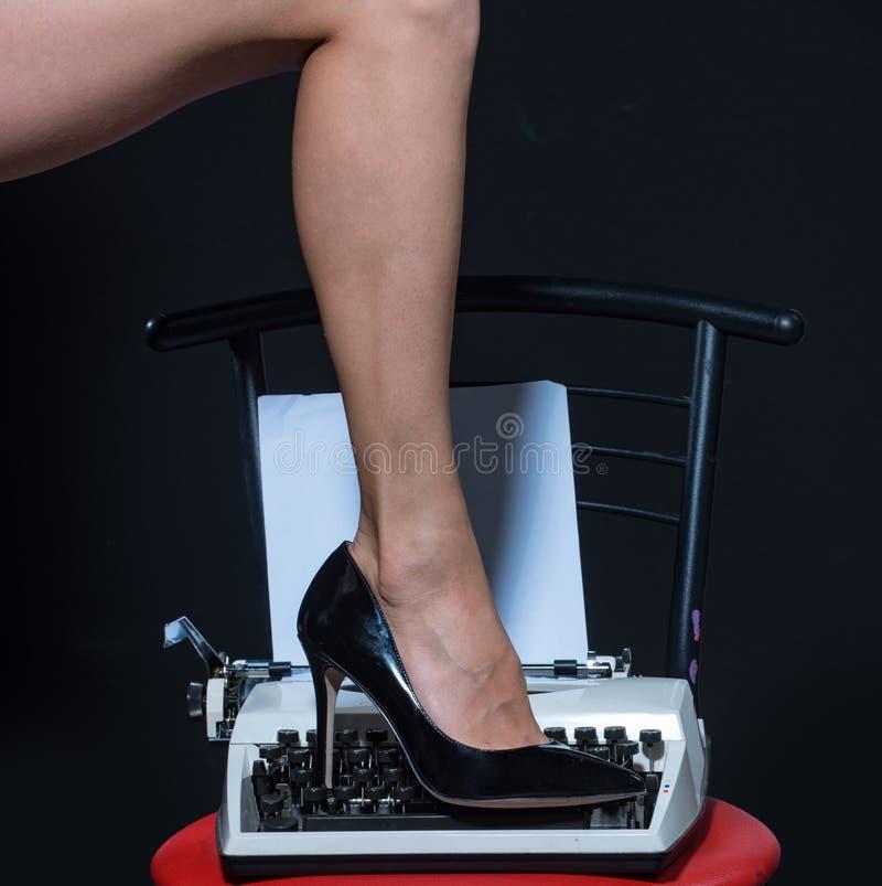 Sexy benen Retro schrijfmachine Moderne manier de schoenen van de amuletslijtage op been van vrouw De verleiding van u Liefdeonde stock afbeelding