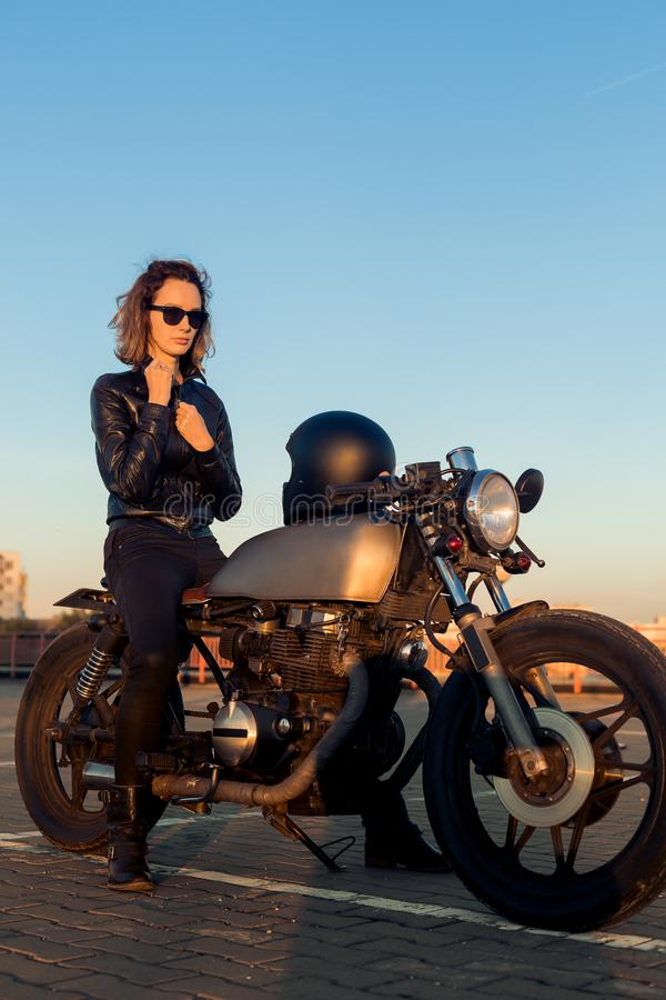 Biker girl on caferacer motorcycle. Biker beautiful woman in black leather jacket sit on vintage custom caferacer motorcycle. Urban roof parking, sunset in big royalty free stock photo