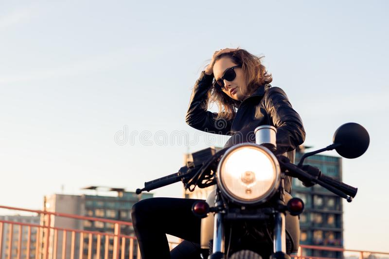 Biker girl on caferacer motorcycle. Biker female in black leather jacket and sunglasses sit on vintage custom caferacer motorcycle. Urban roof parking, sunset royalty free stock photography