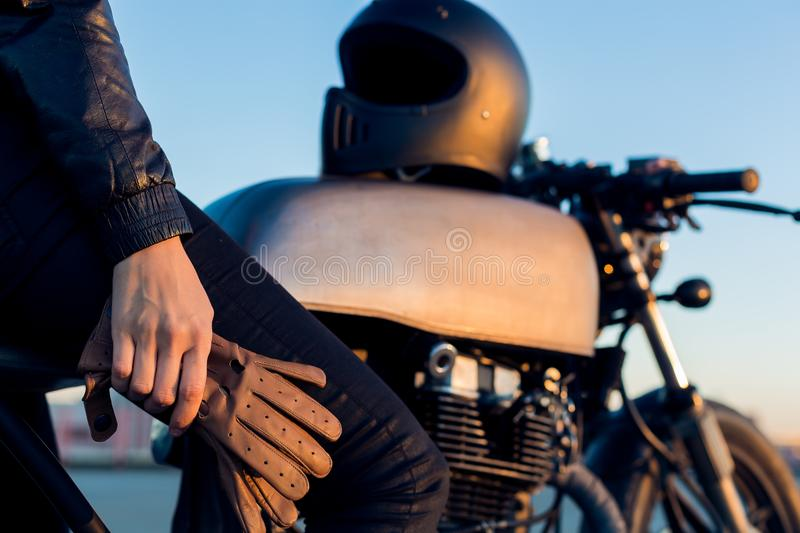 Biker girl on caferacer motorcycle. Biker lady sit on vintage custom caferacer motorcycle. Black full face helmet and leather gloves. Urban roof parking, sunset royalty free stock photos