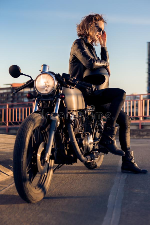 Biker girl on caferacer motorcycle. Biker woman in black leather jacket sit on vintage custom caferacer motorcycle and correct sunglasses. Urban roof parking stock photos