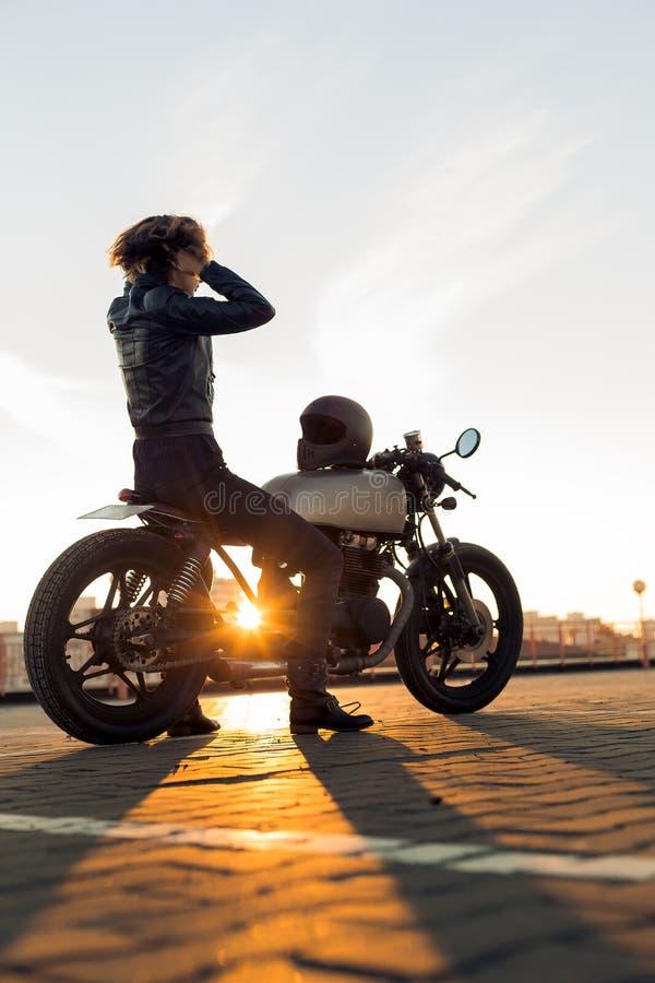 Biker girl on caferacer motorcycle. Biker woman in black leather jacket sit on vintage custom caferacer motorcycle and touch her hair. Urban roof parking stock photography