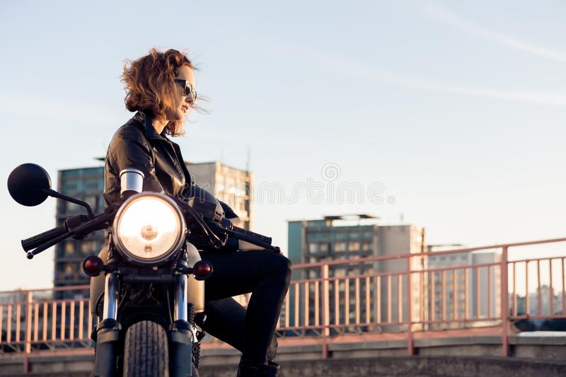 Biker girl on caferacer motorcycle. Biker woman in black leather jacket and sunglasses sit on vintage custom caferacer motorcycle. Urban roof parking, sunset in stock photography