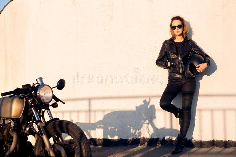 Biker girl on caferacer motorcycle. Biker woman in black leather jacket and sunglasses with vintage custom caferacer motorcycle near wall. Urban roof parking stock photography
