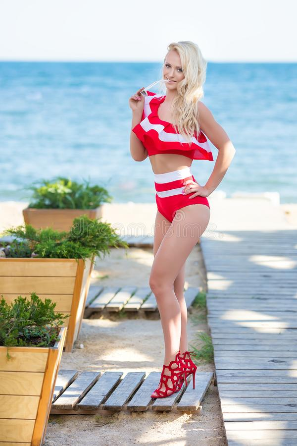 Bikini body woman sun tanning relaxing on perfect tropical beach and turquoise ocean water. Sensual Seducing lady model. Walking in fashion red swimwear with royalty free stock photography