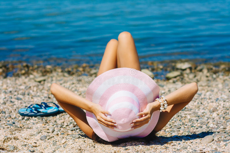bikini woman tanning relaxing on beach. Unrecognizable female adult from the back lying down with straw hat sunbathing under stock photography