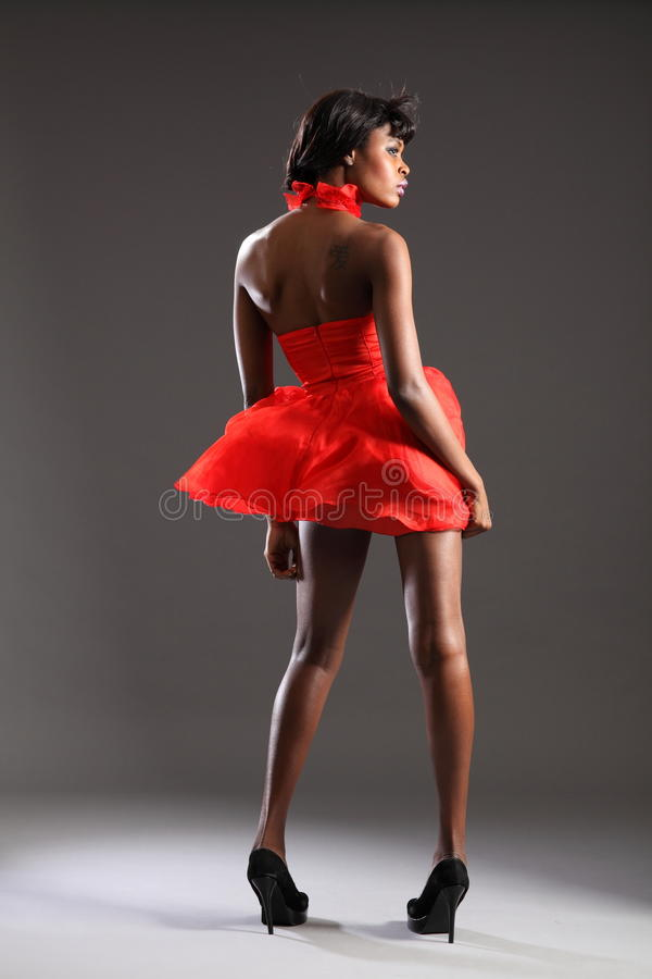 black fashion model in red dress and heels stock image