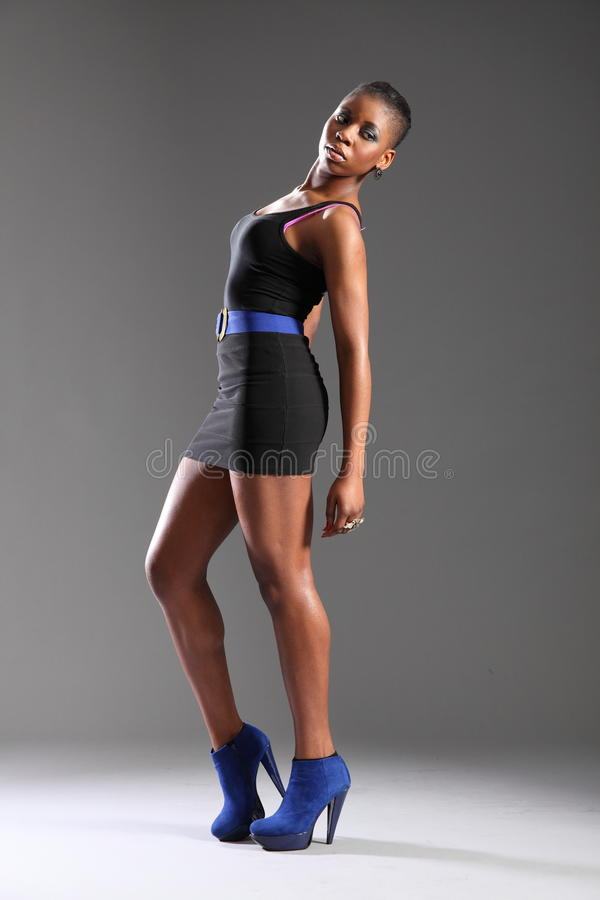 black fashion model in short dress and heels royalty free stock photography