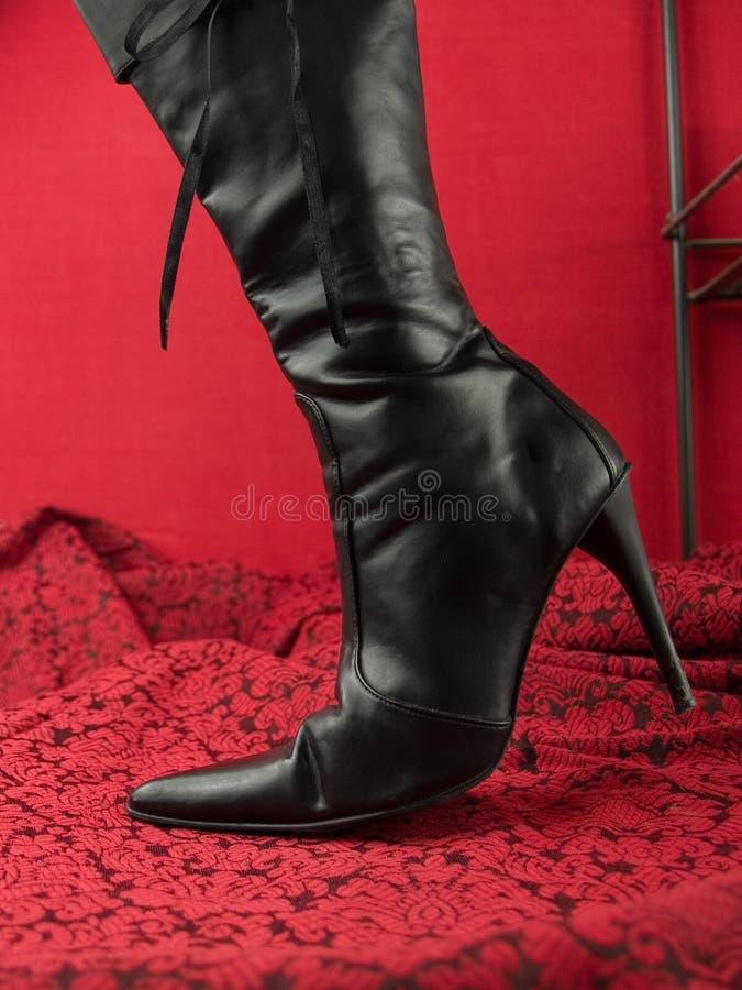 Black stiletto heel boot. Black high stiletto heel boot on red stock photo