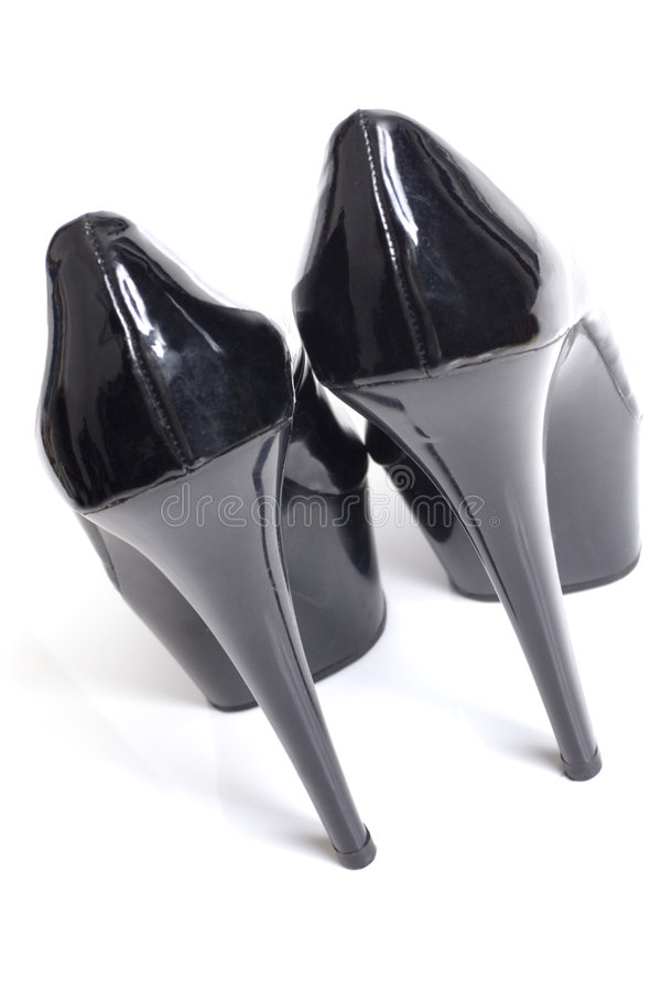Black stiletto high heels from the back. Women's black five inch stiletto patent leather platform shoes. White background royalty free stock images