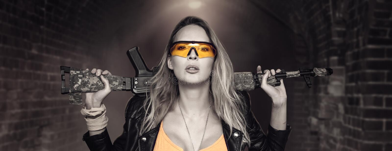 Blond dangerous woman with automatic rifle. Wearing Leather Jacket and yellow glasses stock photos
