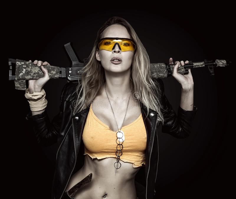 Blond dangerous woman with automatic rifle. Wearing Leather Jacket and yellow glasses on black background royalty free stock photo