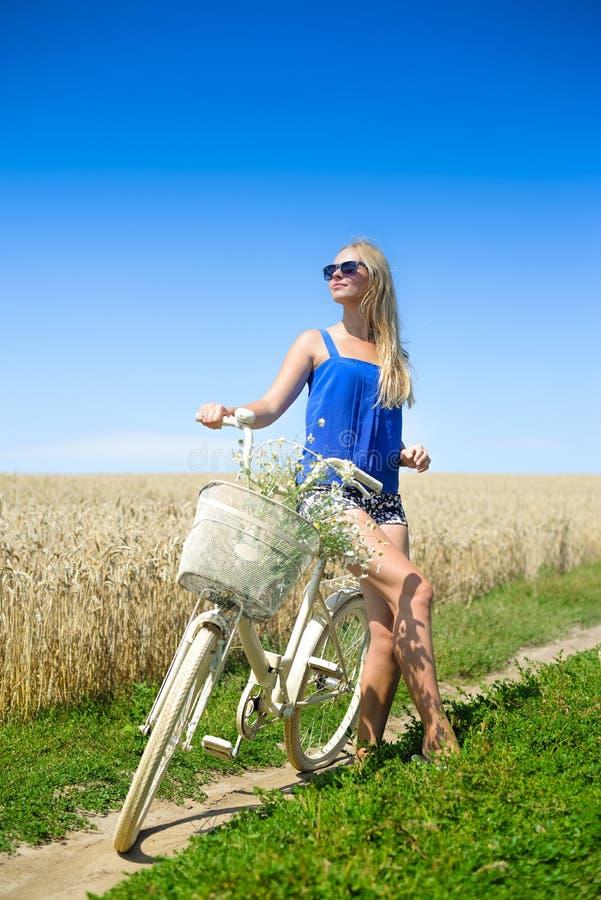 Sexy blond meisje op witte fiets in de zonnige zomer royalty-vrije stock foto