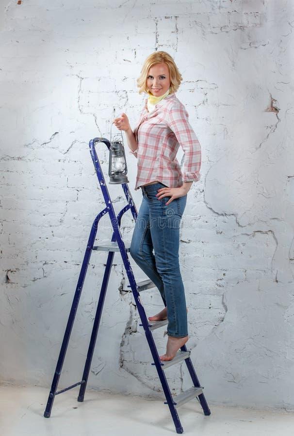 Sexy blond model met aangestoken lantaarn die zich op trapladder bevinden royalty-vrije stock afbeelding