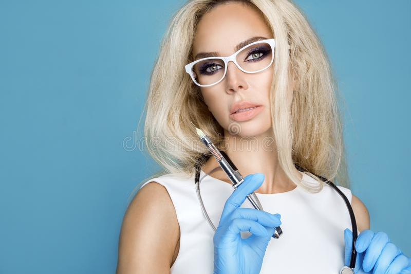 Blond nurse in glasses, holding a stethoscope. And a syringe royalty free stock photo