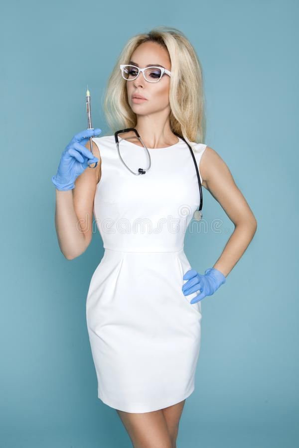 Blond nurse in glasses, holding a stethoscope. And a syringe stock photo
