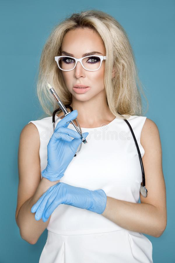 Blond nurse in glasses, holding a stethoscope. And a syringe royalty free stock images