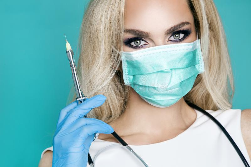 Blond nurse in glasses, holding a stethoscope. And a syringe stock image