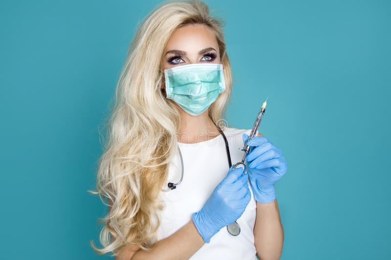 Blond nurse in glasses, holding a stethoscope. And a syringe royalty free stock photos