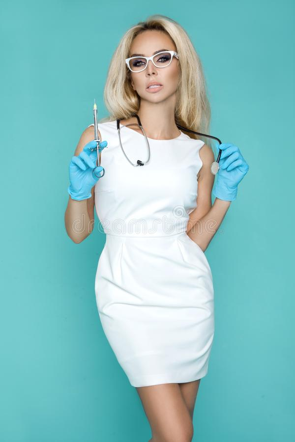 Blond nurse in glasses, holding a stethoscope. And a syringe stock images