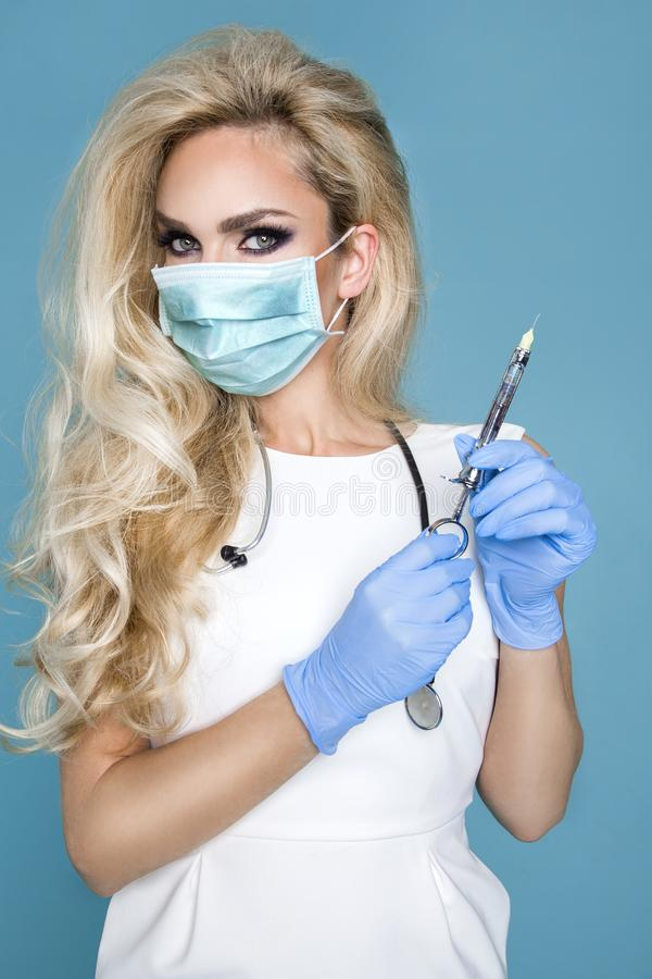 Blond nurse in glasses, holding a stethoscope. And a syringe royalty free stock photography