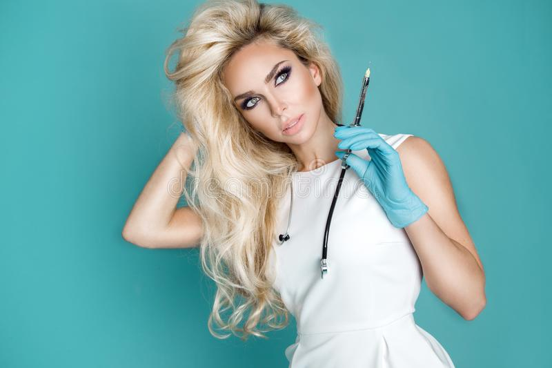Blond nurse in glasses, holding a stethoscope. And a syringe stock photos