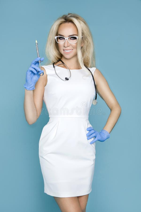 Blond nurse in glasses, holding a stethoscope. And a syringe royalty free stock image