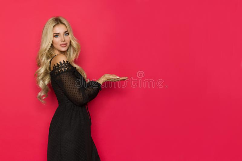 Sexy Blond Woman In Black Dress Holding Hands Raised, Presenting Something And Looking At Camera royalty free stock images