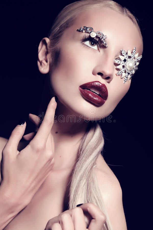 Blond woman with fantastic makeup with bijou accessories. Fashion studio portrait of beautiful woman with blond hair with fantastic makeup with bijou accessories stock images