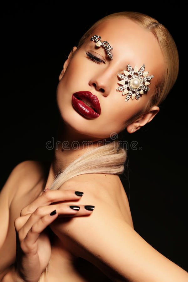 Blond woman with fantastic makeup with bijou accessories. Fashion studio portrait of beautiful woman with blond hair with fantastic makeup with bijou accessories royalty free stock images