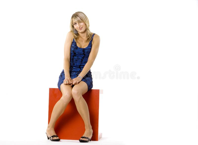 blond woman sitting on red table royalty free stock photos