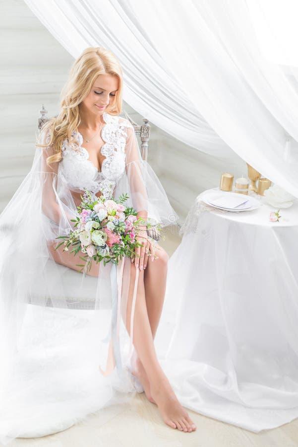 Sexy blonde die in transparante kleding smilingly kijken royalty-vrije stock foto