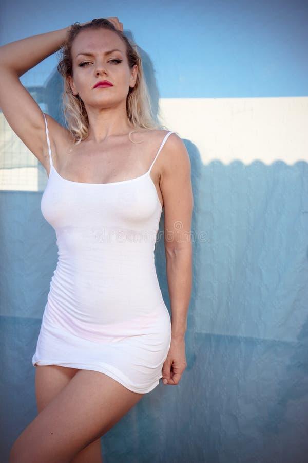 Sexy blonde in een wit overhemd op een terras in de zomer stock foto