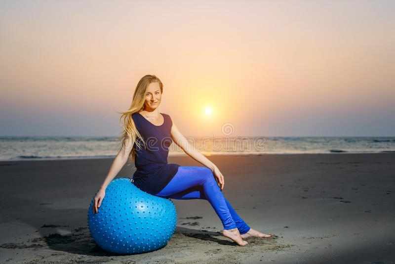 Sexy blonde with fitness ball on the beach outdoors. Beauty sits on a big blue ball in the evening light against sunset. Over the sea and looks at camera royalty free stock images
