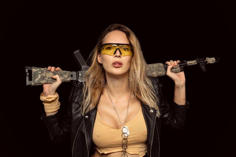 Sexy blonde gefährliche Frau mit automatischem Gewehr lizenzfreie stockfotos
