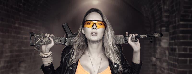 Sexy blonde gefährliche Frau mit automatischem Gewehr stockfotos