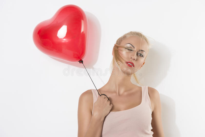 Blonde girl with balloon and hand near the shoulder. Blonde girl with heart shaped balloon, her right hand is near the right shoulder, she looks in to the lens royalty free stock images
