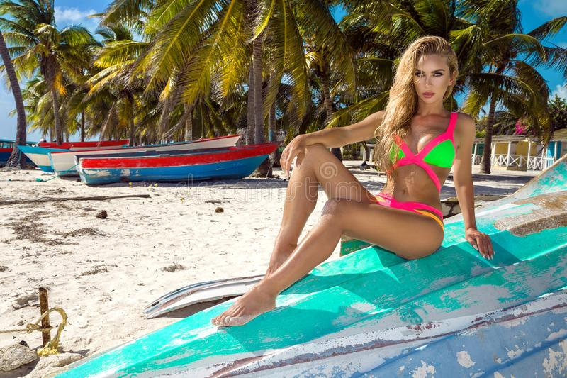 Sexy blonde girl on the beach with palms and blue sky royalty free stock image