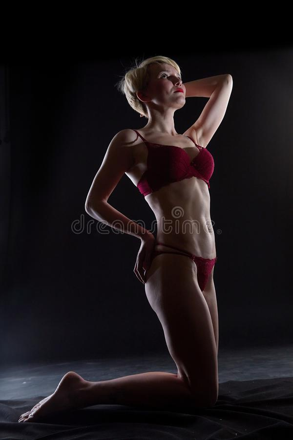 Sexy blonde girl during professional photo shoot in dark room. Model in a red swimsuit royalty free stock photos