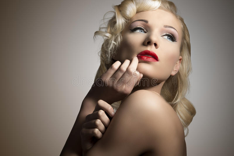 Blonde girl with vintage style. Close-up beauty portrait of pretty blonde girl with retro hair style and make-up in diva pose royalty free stock image
