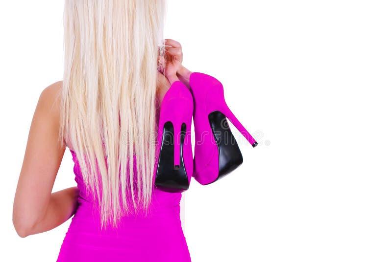 sexy blonde junge Frau, die Pinkschuhe getrennt anhält stockbild