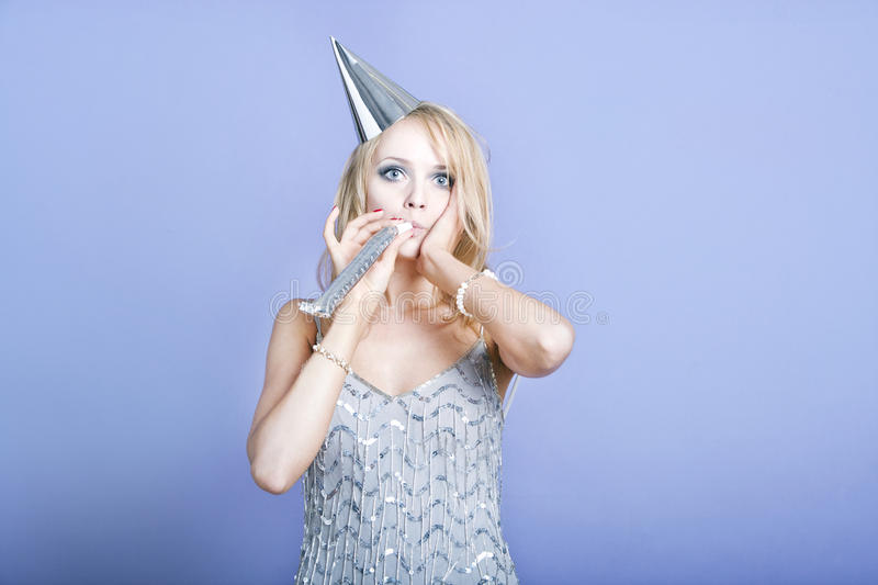 Blonde party girl wearing silver dress and blowing party whistle stock images