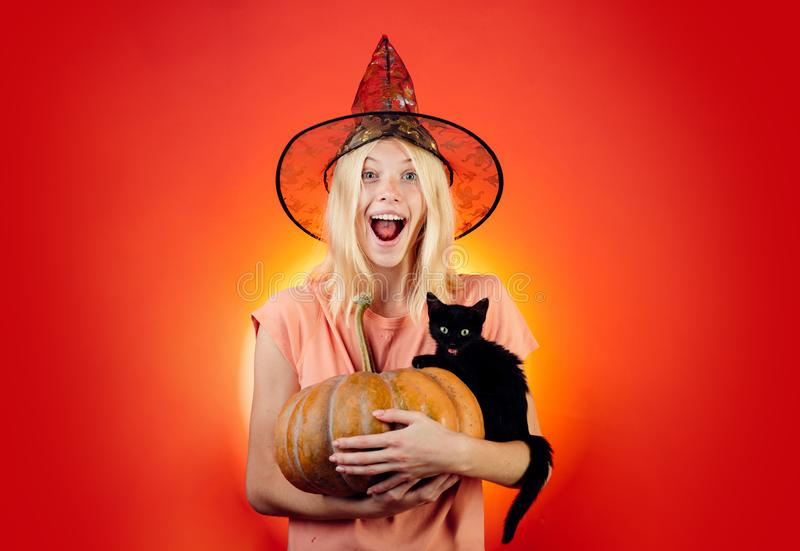 Blonde with Pumpkin and black cat. Halloween concept. Ready for text slogan or product. Halloween wide poster for. Witch with Pumpkin and black cat. Halloween royalty free stock image