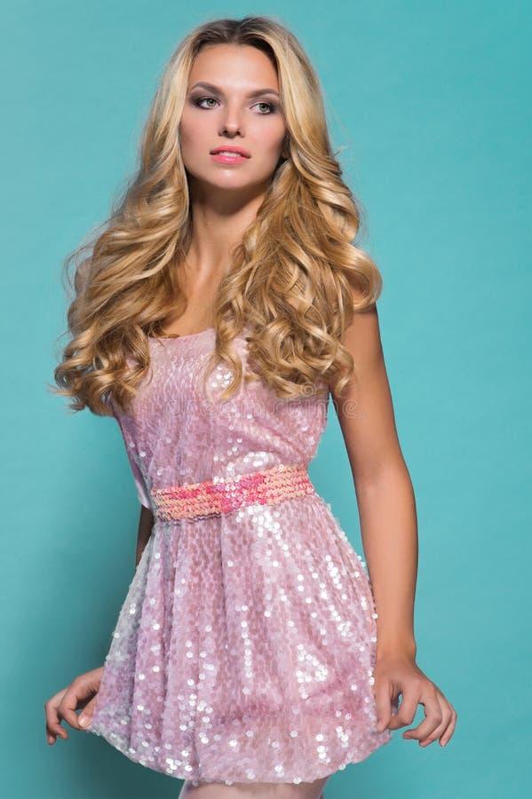Sexy blonde vrouw in korte roze kleding stock fotografie